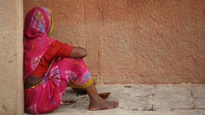 Una mujer sentada en una acera, en India.