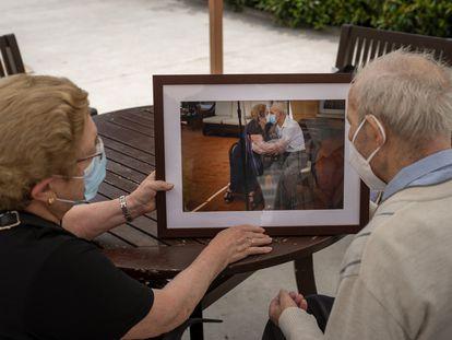Agustina Cañamero y Pascual Pérez miran, en la residencia donde viven en Barcelona, la fotografía que les tomó Emilio Morenatti en su reencuentro tras 102 días sin verse por la pandemia.