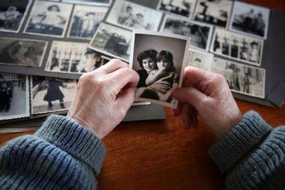 Una mujer observa una foto antigua de ella con su hija.