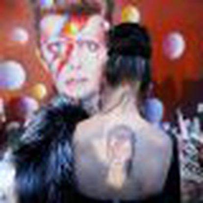 A woman with a Ziggy Stardust tattoo visits a mural of David Bowie in Brixton, south London