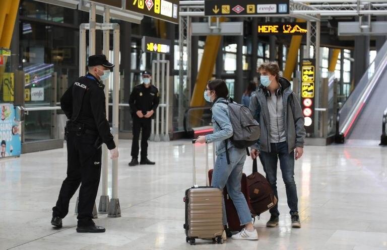 Dos viajeros y dos agentes, en el aeropuerto de Barajas el martes.