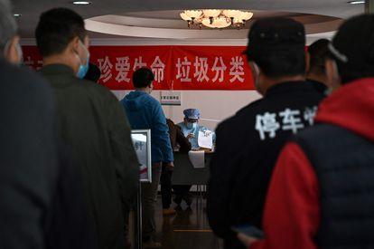 Un sanitario registra a ciudadanos que quieren recibir la vacuna contra la covid en un centro comunitario en Pekín, el 8 de abril.
