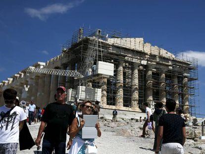 Los turistas visitan el templo del Partenón en la Acrópolis de Atenas, Grecia.