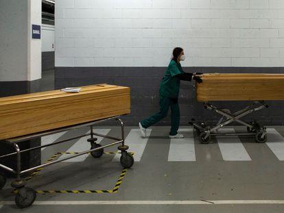 Una trabajadora de la funeraria Mémora traslada féretros con los restos mortales de víctimas de covid en el Tanatorio de Sancho de Ávila de Barcelona, este lunes.