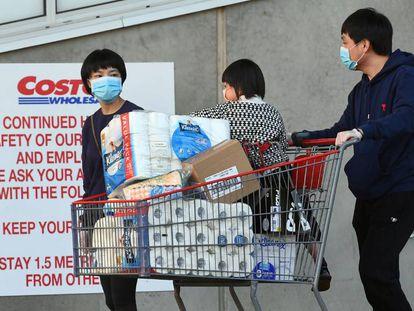 Clientes de un supermercado Costco, en Melbourne, Australia, con un carrito lleno de papel higiénico.