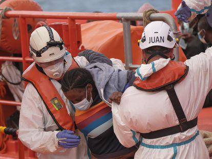 Una mujer rescatada de una patera es ayudada en el puerto de Arguineguín, el 12 de abril.