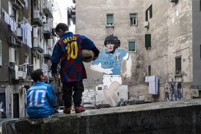 Dos niños lucen las camisetas de Maradona y Messi en el barrio de Forcella (Nápoles).