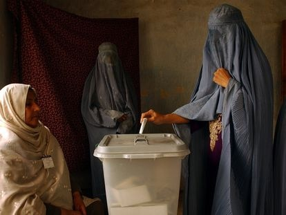 Una mujer afgana con burka mete su papeleta en una urna en Kabul en 2004, en las primeras elecciones presidenciales del país.