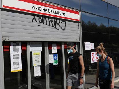Dos jóvenes pasan ante una oficina de empleo en Madrid, en mayo pasado.