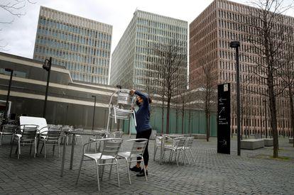 Una camarera prepara la terraza del restaurante donde trabaja para atender a sus clientes, en L'Hospitalet de Llobregat.