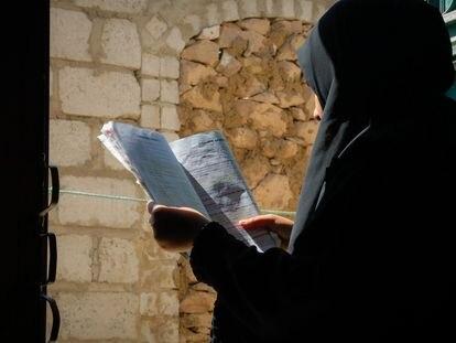 Asma'a, una niña de 15 años que se libró del matrimonio infantil, lee un libro desde el patio de su casa en Dhamar, Yemen.