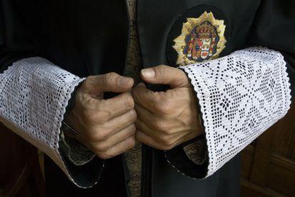 Las manos de un juez sobresalen de las puñetas de la toga.