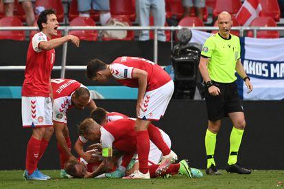 Los jugadores de Dinamarca atienden a Eriksen sobre el césped.