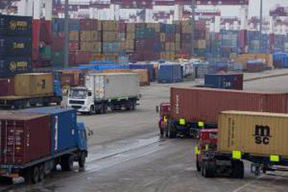 Varios camiones transportan contenedores en un  puerto. EFE/Archivo