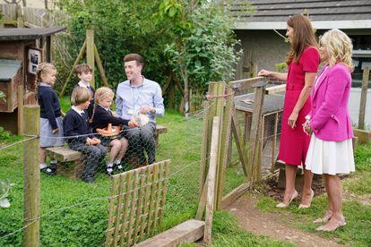 Kate Middleton y Jill  Biden conversan con un grupo de niños mientras estos alimentan a los conejos.