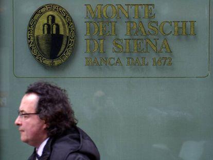 Un hombre camina por delante de una oficina del banco Monte dei Paschi en Siena.