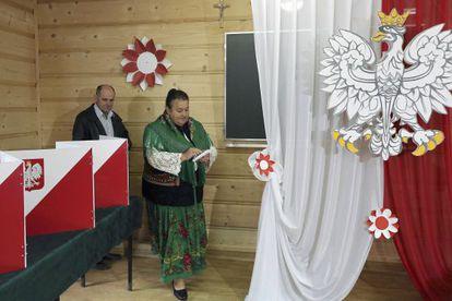 Una mujer vestida con el traje tradicional vota en un colegio eletoral en Zakopane.