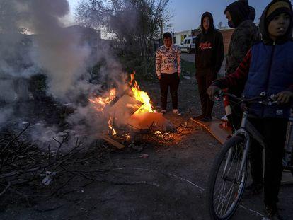 Un grupo de jóvenes alrededor de una fogata al caer la tarde en la Cañada Real en diciembre.