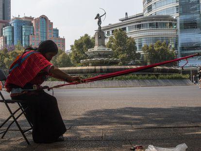 Una mujer realiza una manta bordada con un telar de cintura en la banqueta de avenida Paseo de la Reforma.
