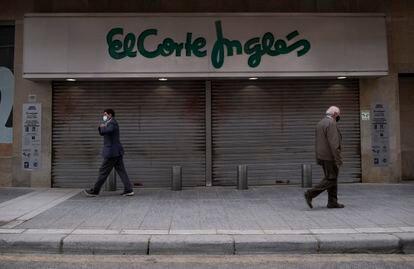 Dos personas pasan delante de la entrada de El Corte Inglés de Linares, en Jaén, el pasado 5 de marzo.