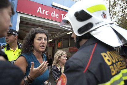 Una pasajera de los trenes afectados habla con un bombero tras el rescate en Barcelona.