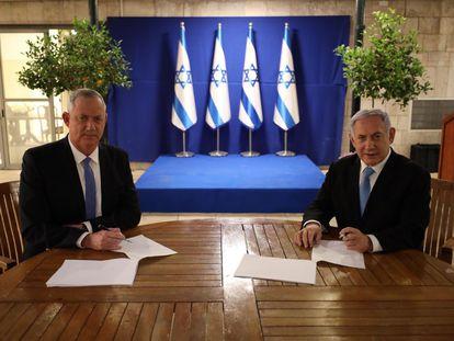 Netanyahu, a la derecha, firma junto al centrista Beny Gantz el acuerdo alcanzado este lunes.