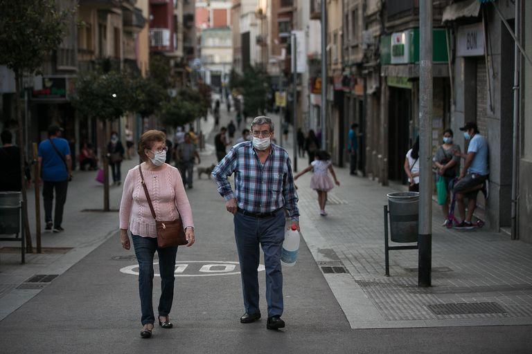 Dos personas caminan por el barrio de La Torrassa, en L'Hospitalet de Llobregat, Barcelona, el punto de mayor densidad de población de Europa, según un estudio.