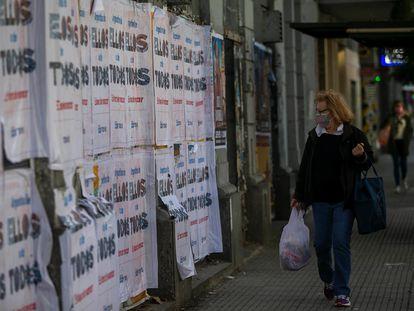 Una mujer camina frente a una pared cubierta con publicidad electoral en Buenos Aires.
