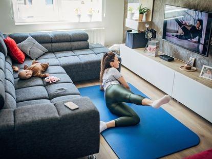 Una madre hace ejercicio frente al televisor mientras su bebé descansa en el sofá.