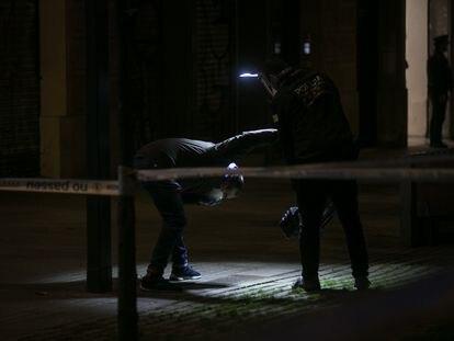 Agentes de investigacion criminal de los Mossos inspeccionan la escena del tiroteo.