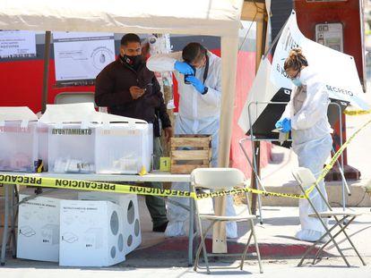 Peritos forenses trabajan en una casilla electoral en Tijuana donde un hombre arrojó una cabeza humana.