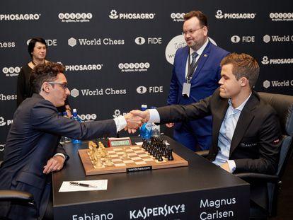 Caruana y Carlsen se saludan al inicio de la 1ª partida del Mundial ante los árbitros, Stéphane Escafre y Nana Alexandria