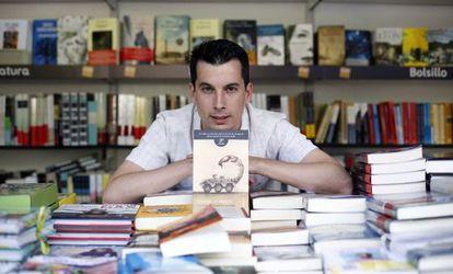 Luis Gonzalo Segura posa con su novela en la Feria del Libro de Madrid, en julio.