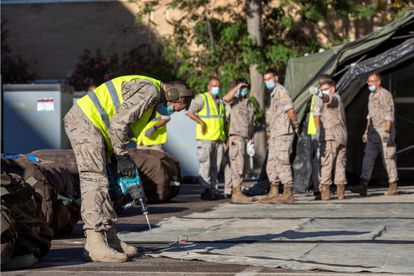Un grupo de militares monta una carpa de triaje en el aparcamiento del Hospital Universitario de Zaragoza.