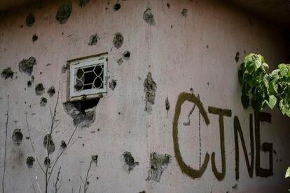 La fachada de una casa agujereada por impactos de bala junto a una pintada con las siglas del Cartel Jalisco Nueva Generación (CJNG) en El Limoncito, en el municipio de Aguililla.