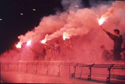 Miembros de los Boixos Nois saludan con bengalas a los jugadores del Barça,  en enero de 1991.