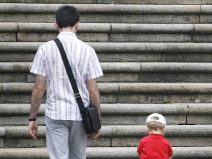 Un padre con su hijo de espaldas ante unas escaleras.