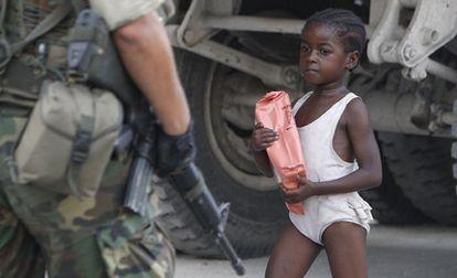Una niña camina en mitad de un cordón de seguridad de los soldados estadounidenses en una calle de Puerto Príncipe.