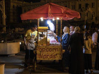 Un grupo de mujeres y una niña, ante un puesto de palomitas en Trípoli.