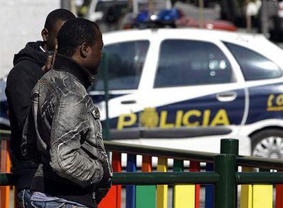 Dos surafricanos, junto a un coche de policía esta mañana en el barrio de Lavapiés.