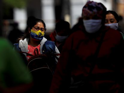 Varias personas con cubrebocas caminan por una calle de Quito, el 25 de agosto.