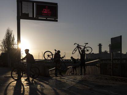 Un grupo de ciclistas saltan la valla de acceso al parque fluvial del Besòs para entrar a pedalear antes de su apertura