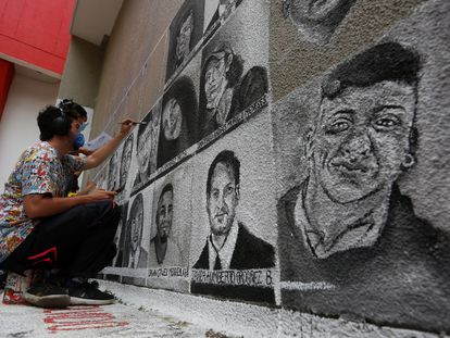 Varios artistas pintan los rostros de algunos de los jóvenes muertos a manos de la policía durante las manifestaciones de protesta en Cali (Colombia), el pasado martes.