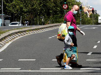 Un niño acompañado de un adulto por el centro de Madrid, este sábado.