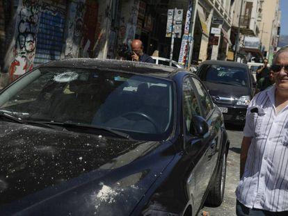 Un hombre junto a un coche dañado tras el terremoto, este viernes en Atenas.