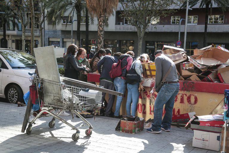 Ciudadanos recogen zapatos y otros objetos de un contenedor el pasado 6 de octubre en Barcelona.