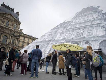 Turistas leen los carteles que indican que el Museo del Louvre permanecerá cerrado para proteger las obras de zonas en riesgo de verse inundadas.