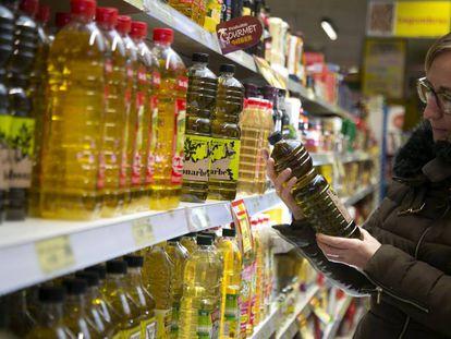 Una mujer mira varias botellas de aceite de oliva en un supermercado.