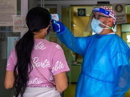 Un sanitario le mide la temperatura a una mujer en la entrada del centro de salud Puerta Bonita en Carabanchel, Madrid.