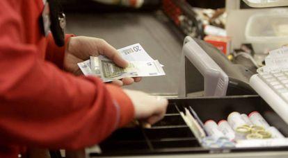 Una cajera de un supermercado devuelve cambio a un cliente.